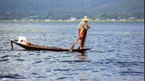 Remando con una pierna y echando las redes en el lago Inle